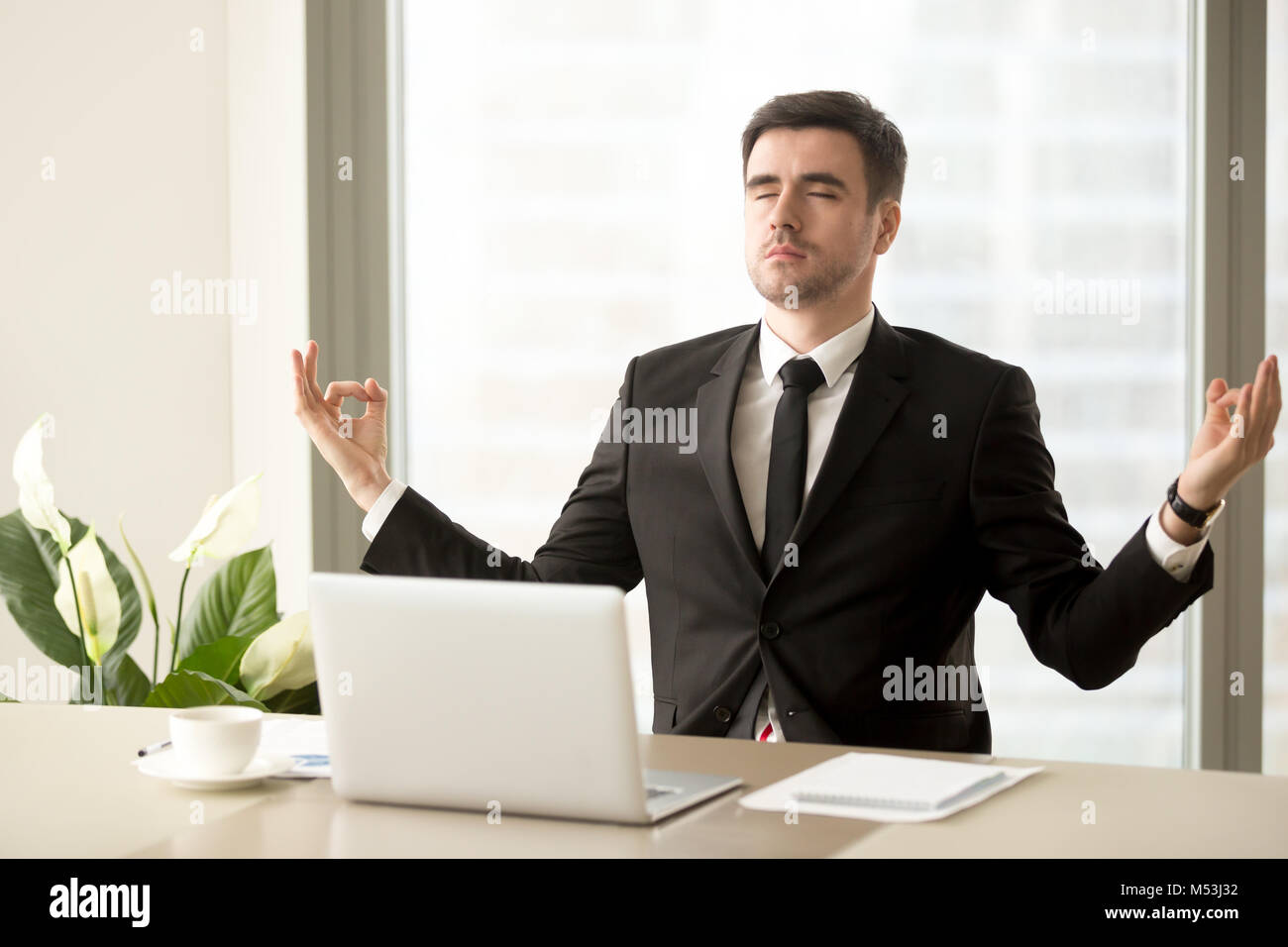 Company leader trying to find calmness at work - Stock Image