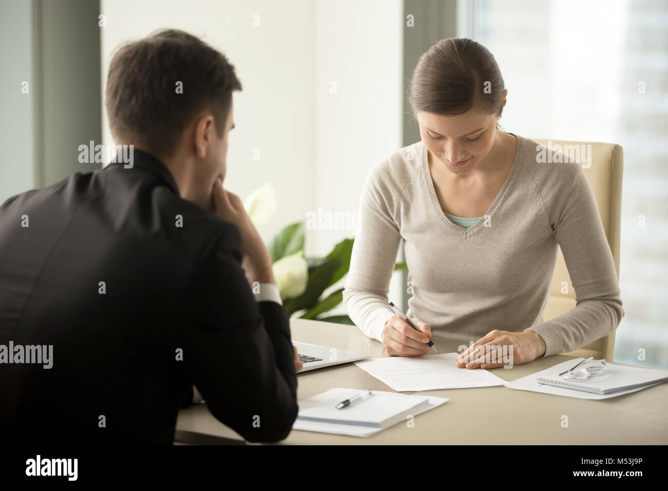 Businesswoman signing contract with businessman - Stock Image