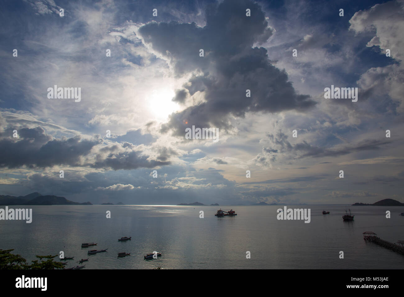 Clouds spectacle turbulent sky and deep rising sun over Flores island sea coastline with anchored boats and ships - Stock Image