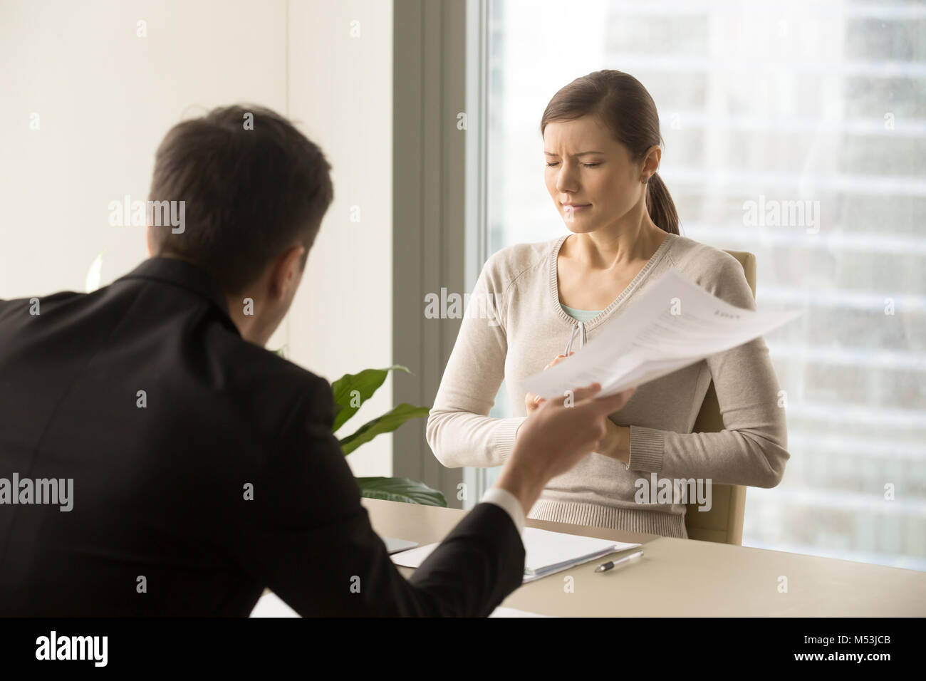 Angry boss scolding scared female employee - Stock Image