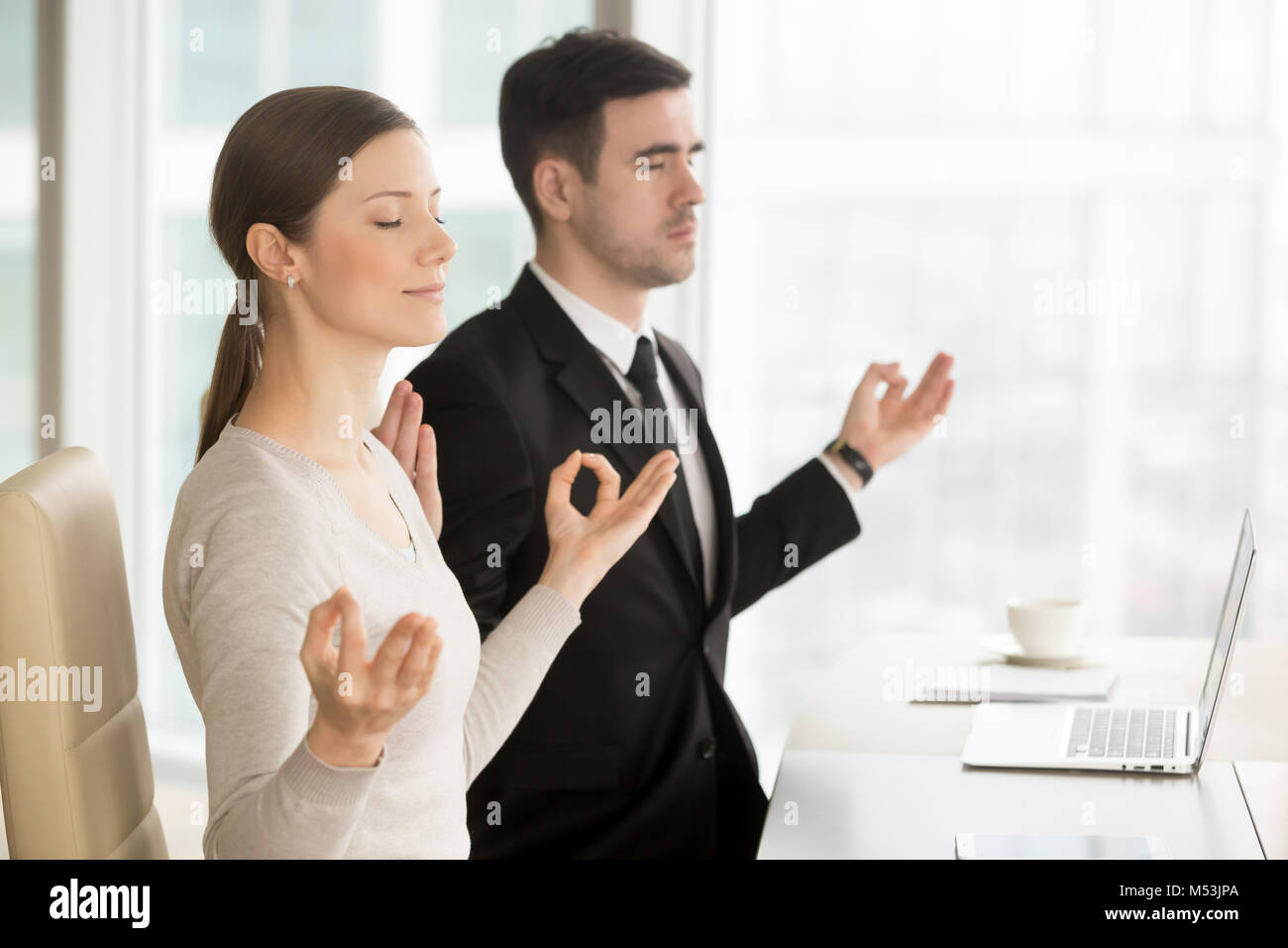 Young business leaders practice yoga at workplace - Stock Image