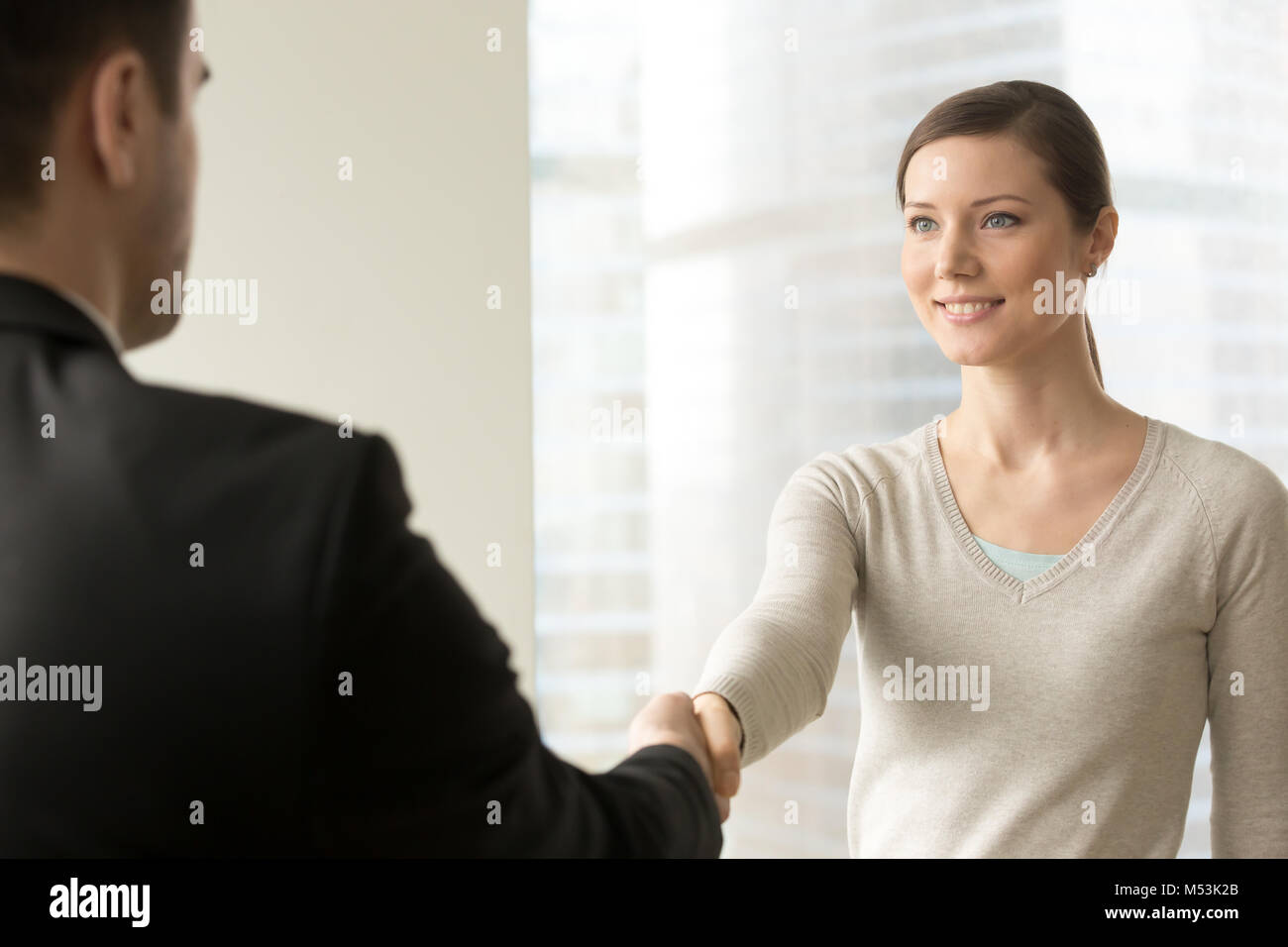 Attractive female employee handshaking with boss - Stock Image