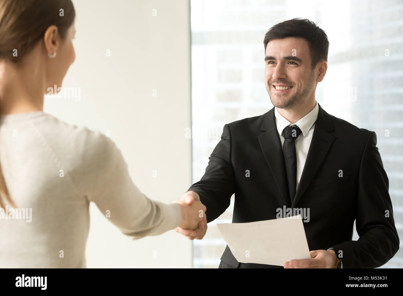 Boss congratulating female employee with promotion - Stock Image