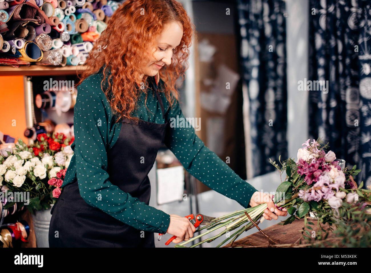 image of pretty girl with red, curly hair making up an attractive bouquet - Stock Image