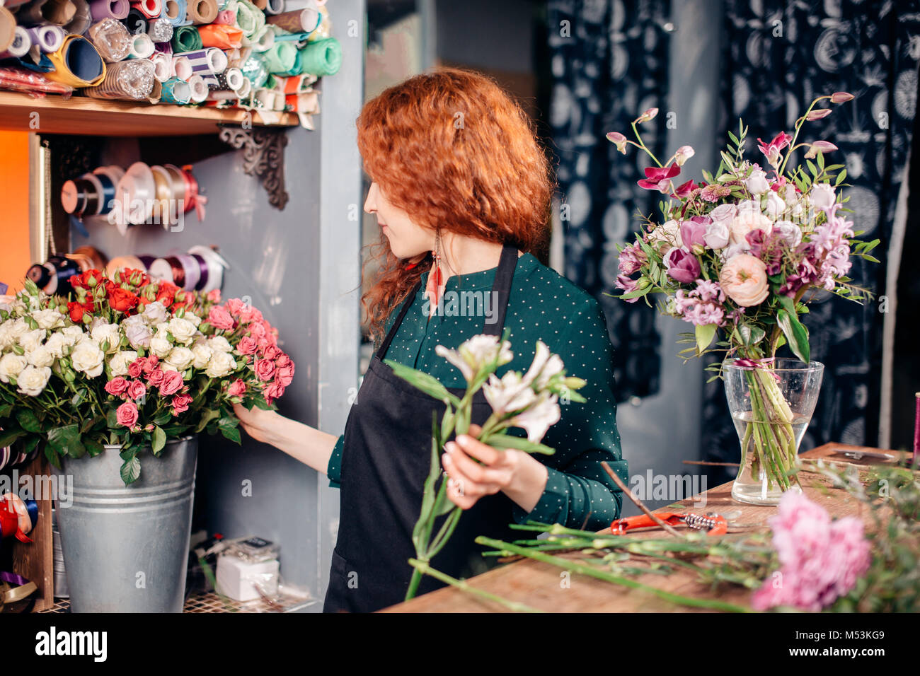 woman making bouquet of different roses. florist working at flower shop - Stock Image