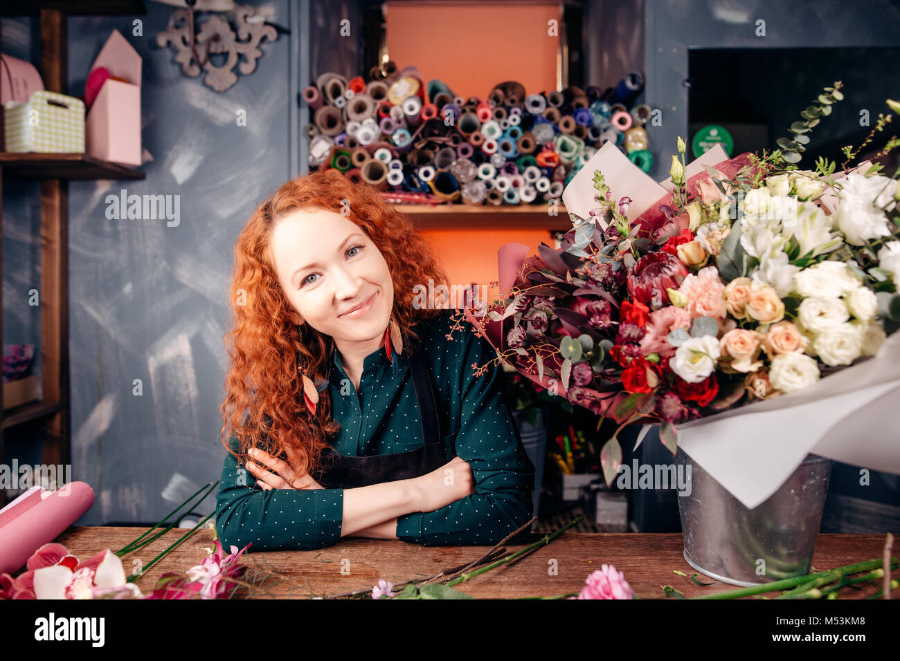 florist-designer with red hair and green eyes working at florist's shop - Stock Image
