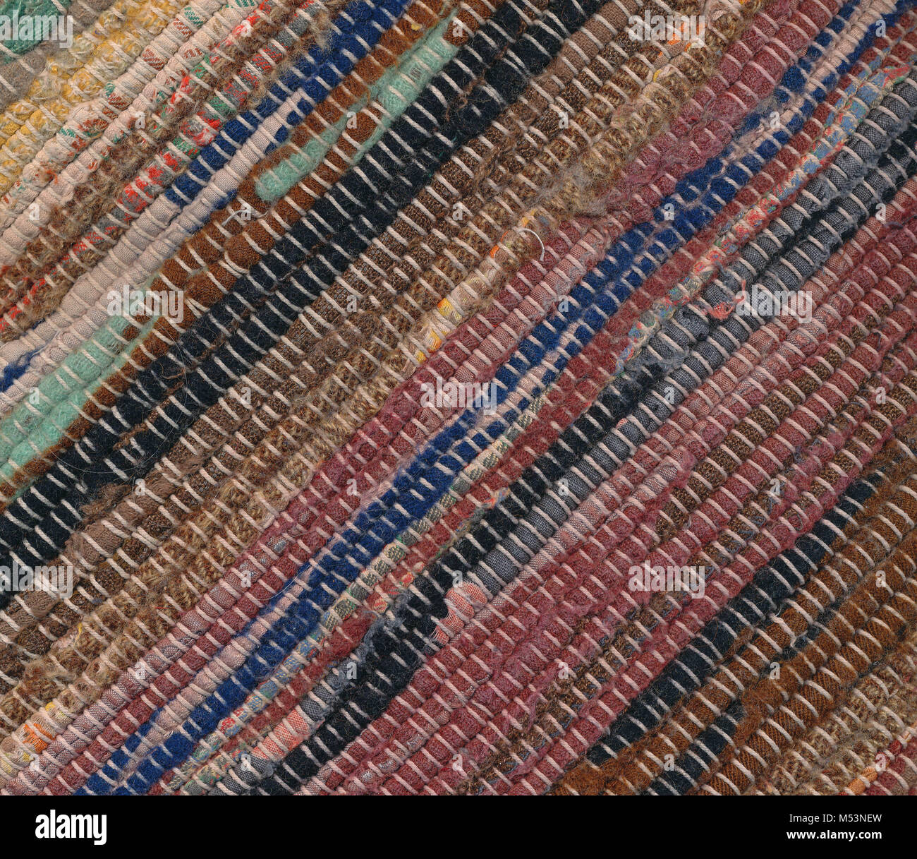 Diagonally closeup of old worn out striped rag rug - Stock Image