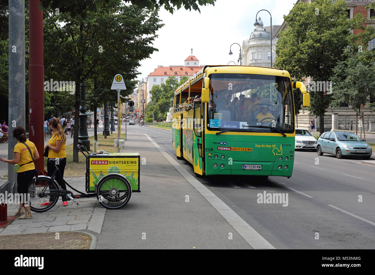 VIENNA, AUSTRIA - JULY 12, 2015: Two Promoters With Cargo Bicycle and Sightseeing Tourist Bus in Vienna, Austria. - Stock Image