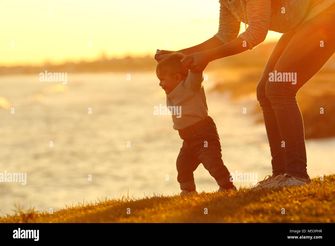 Backlight silhouette of a confident baby learning to walk and his mom helping him at sunset - Stock Image
