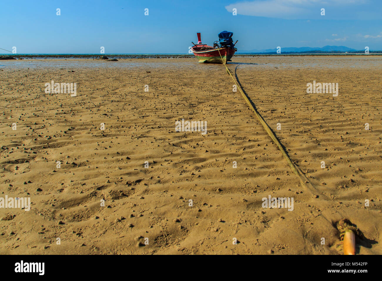 Traditional Thai wooden longtail boats (Rua Hang Yao) moored on the sand at small pier with blue sky and small island Stock Photo