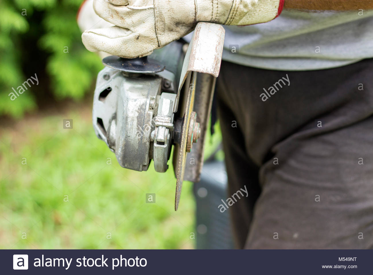 Construction worker using an angle grinder cutting tile - Stock Image