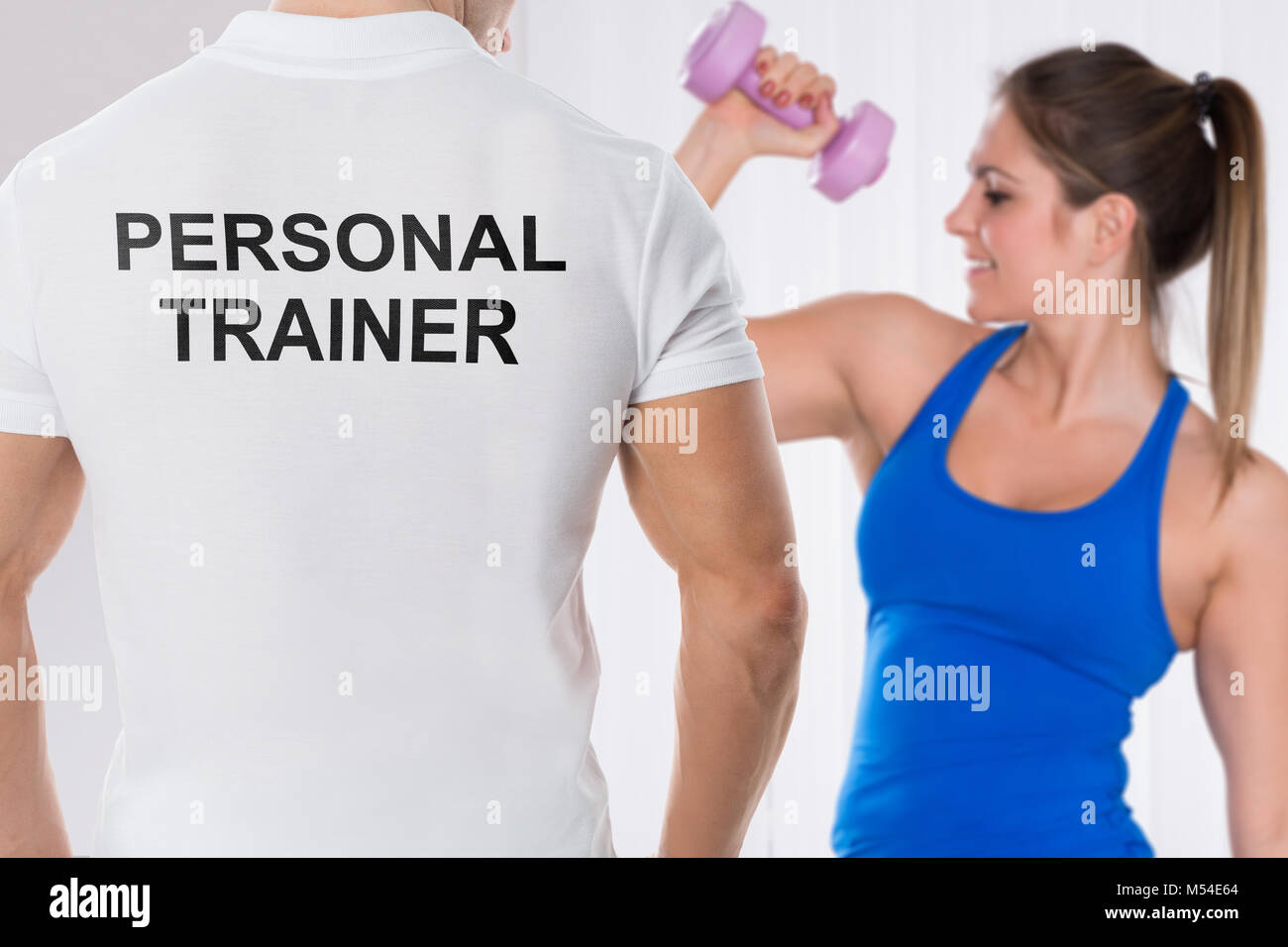 Young Woman Doing Exercise With Dumbbell In Front Of Personal Trainer - Stock Image
