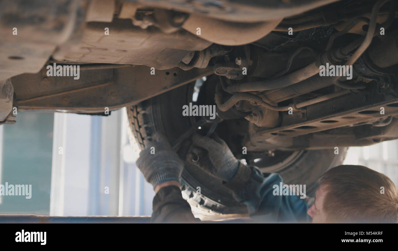 Automobile service - mechanic wrapping working device under car bottom - Stock Image