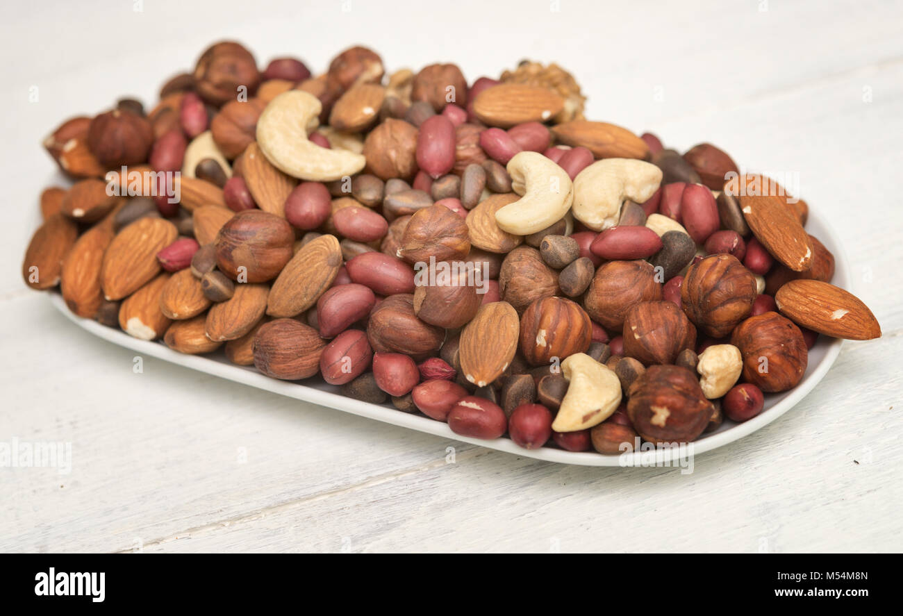 mixed nuts on a plate - Stock Image