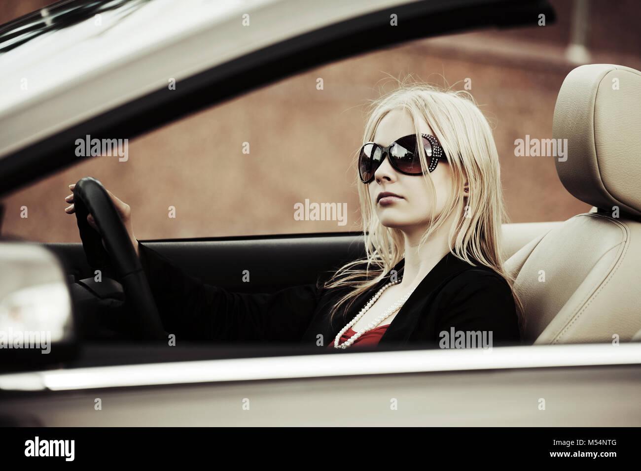 Young woman driving convertible car - Stock Image