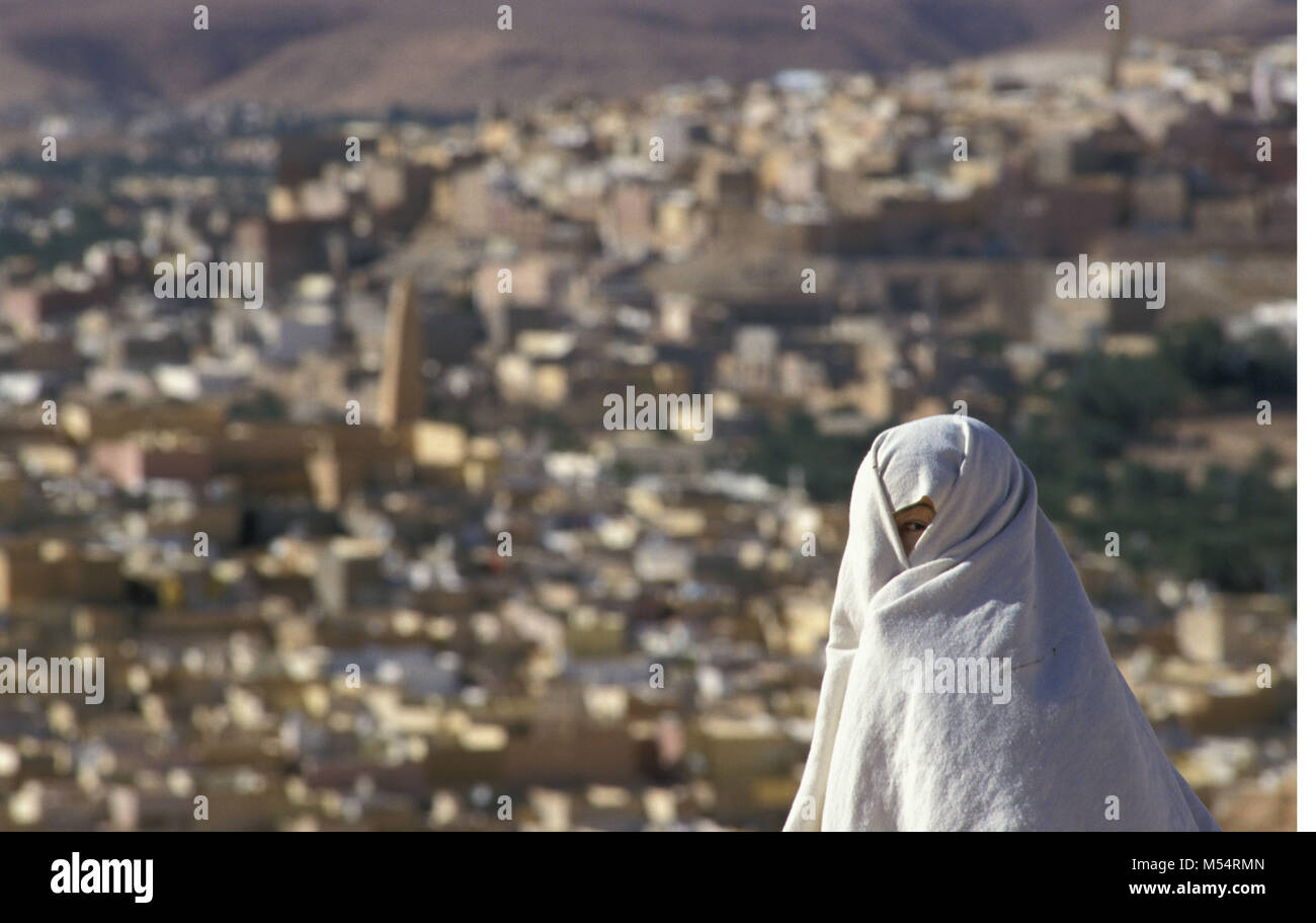 Algeria. Ghardaia. M'zab Valley. Sahara desert. Oasis. Veiled woman in front of city. UNESCO Wolrd Heritage - Stock Image
