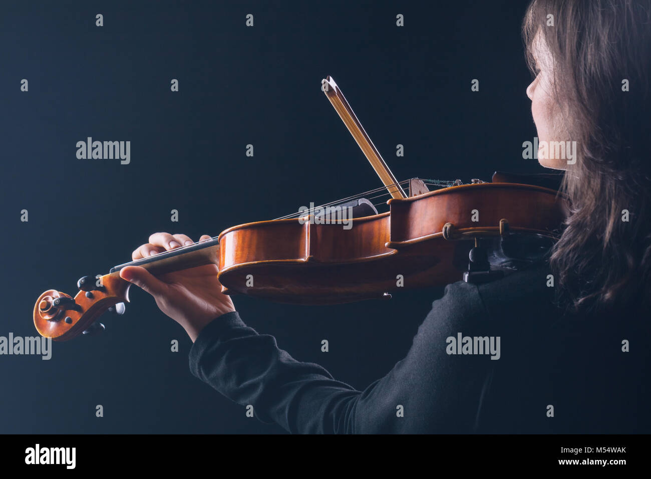 Playing the violin. Woman playing the violin with her back to the camera on a black background - Stock Image