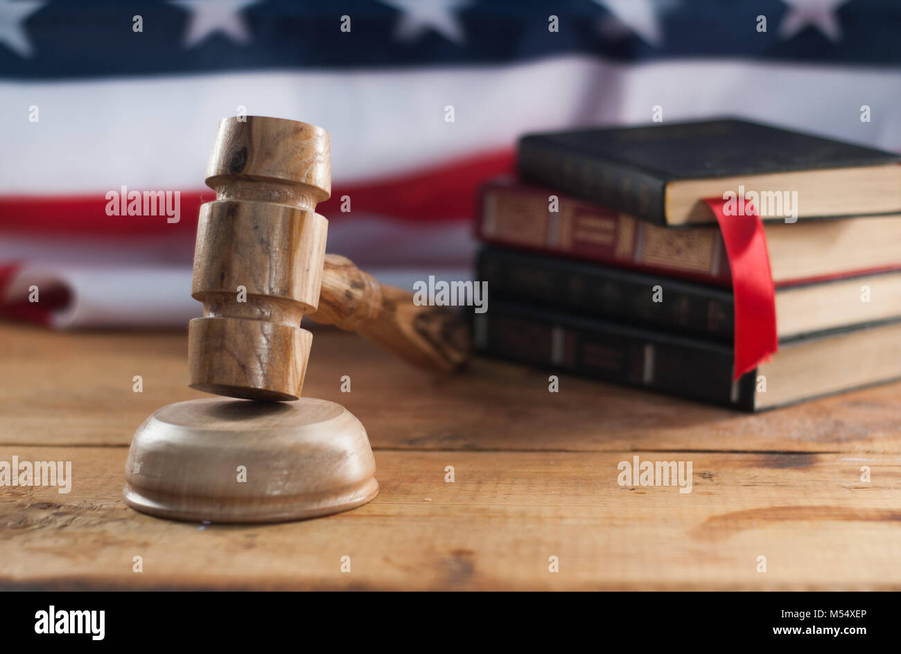 Judges wooden gavel with USA flag in the background. A symbol of jurisdiction. American court - Stock Image