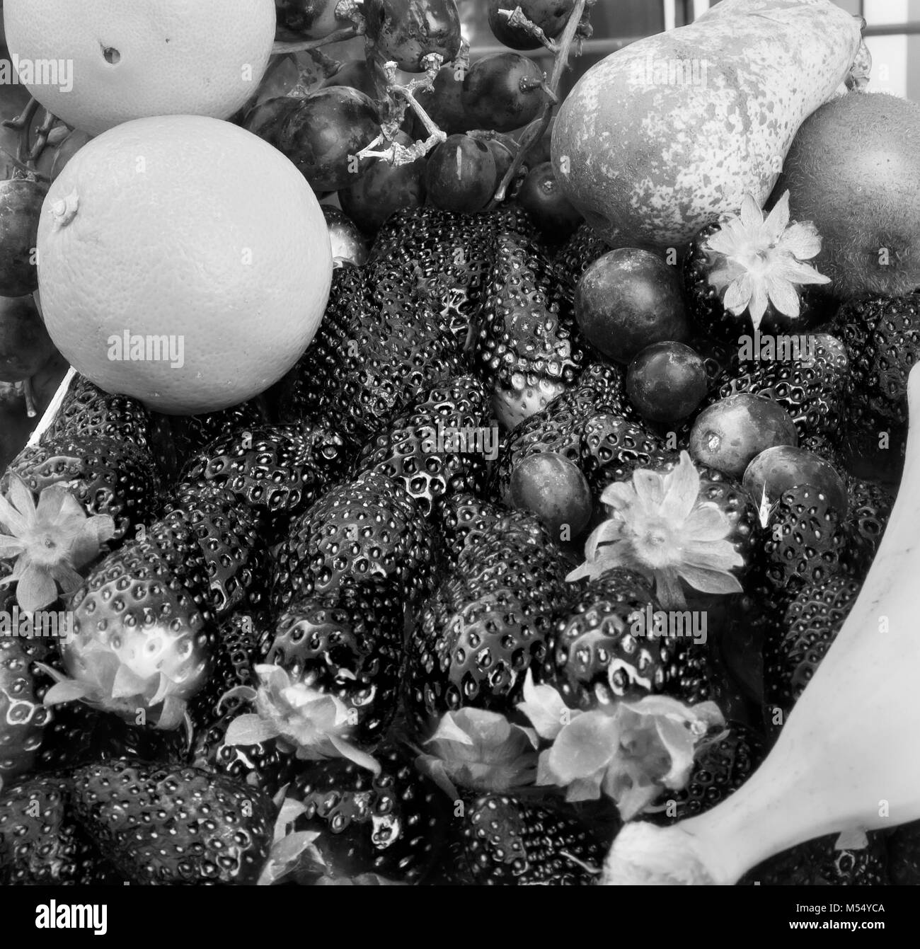 fruit: strawberries oranges grapes kiwi and banana. Black and white photo - Stock Image