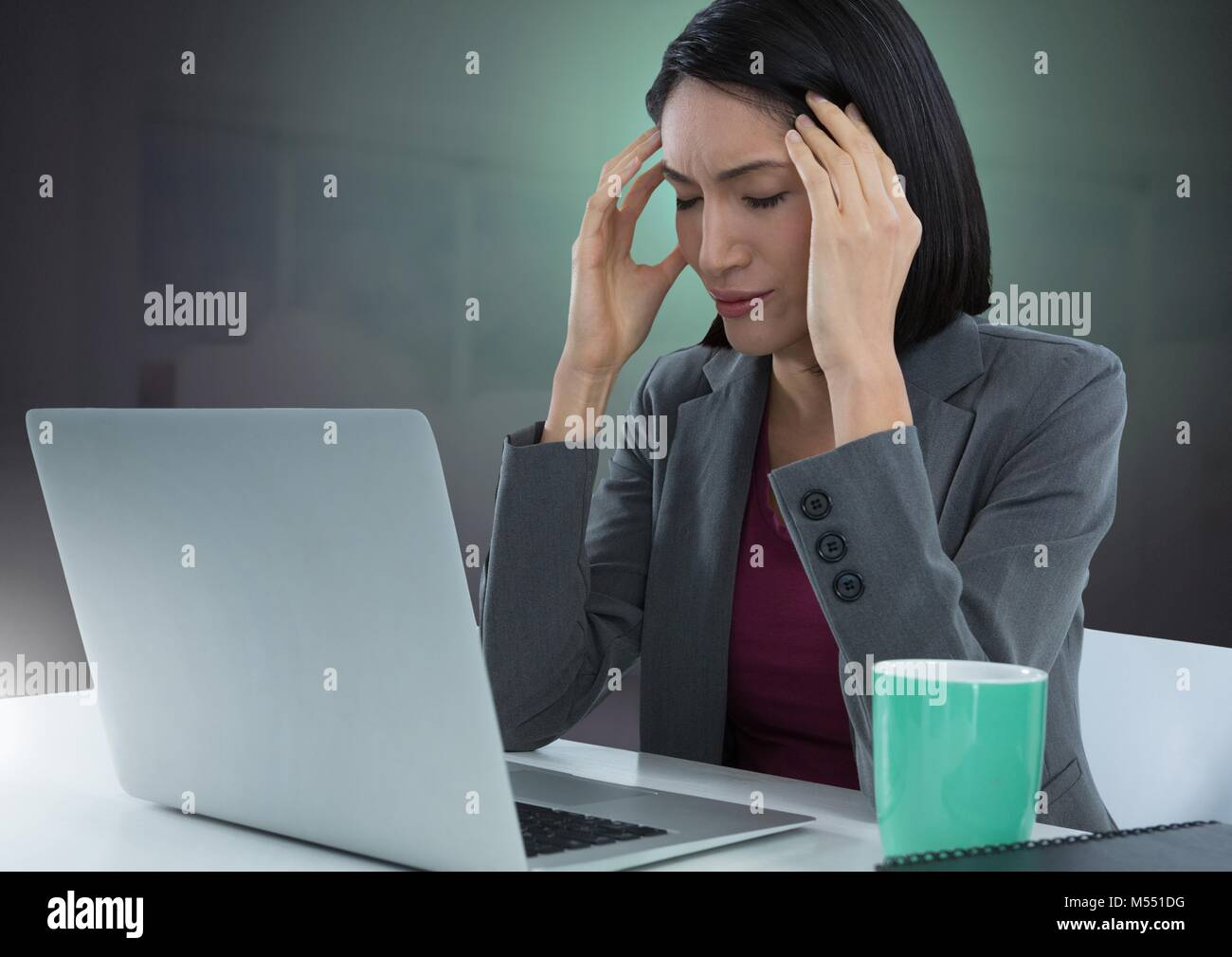 Businesswoman working on laptop with green background Stock Photo