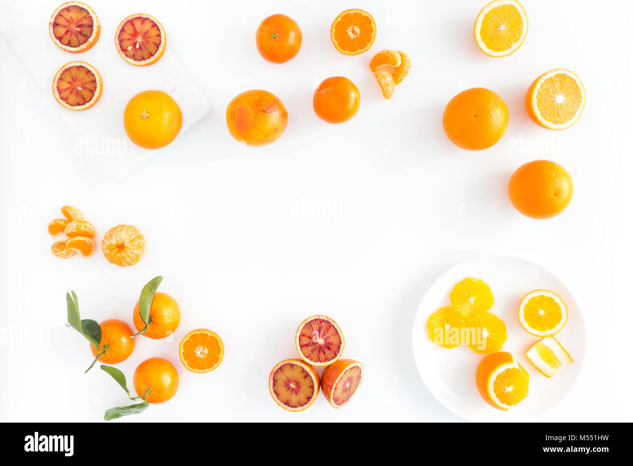 Composition of blood oranges, oranges and  clementines whole, halved, peeled, and sliced arranged on marble board, - Stock Image