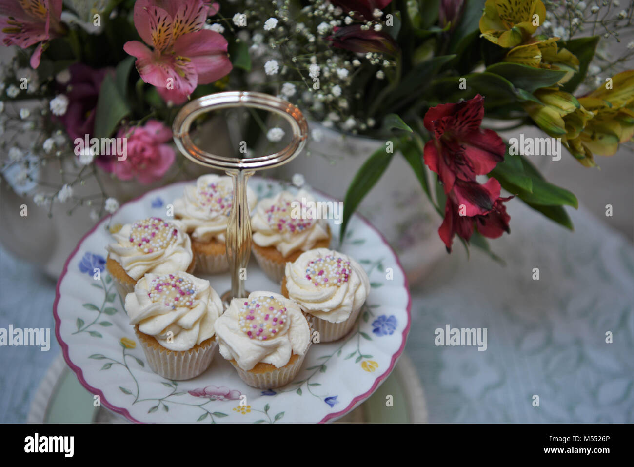 food of cupcakes on a vintage cake stand with fresh flowers - Stock Image