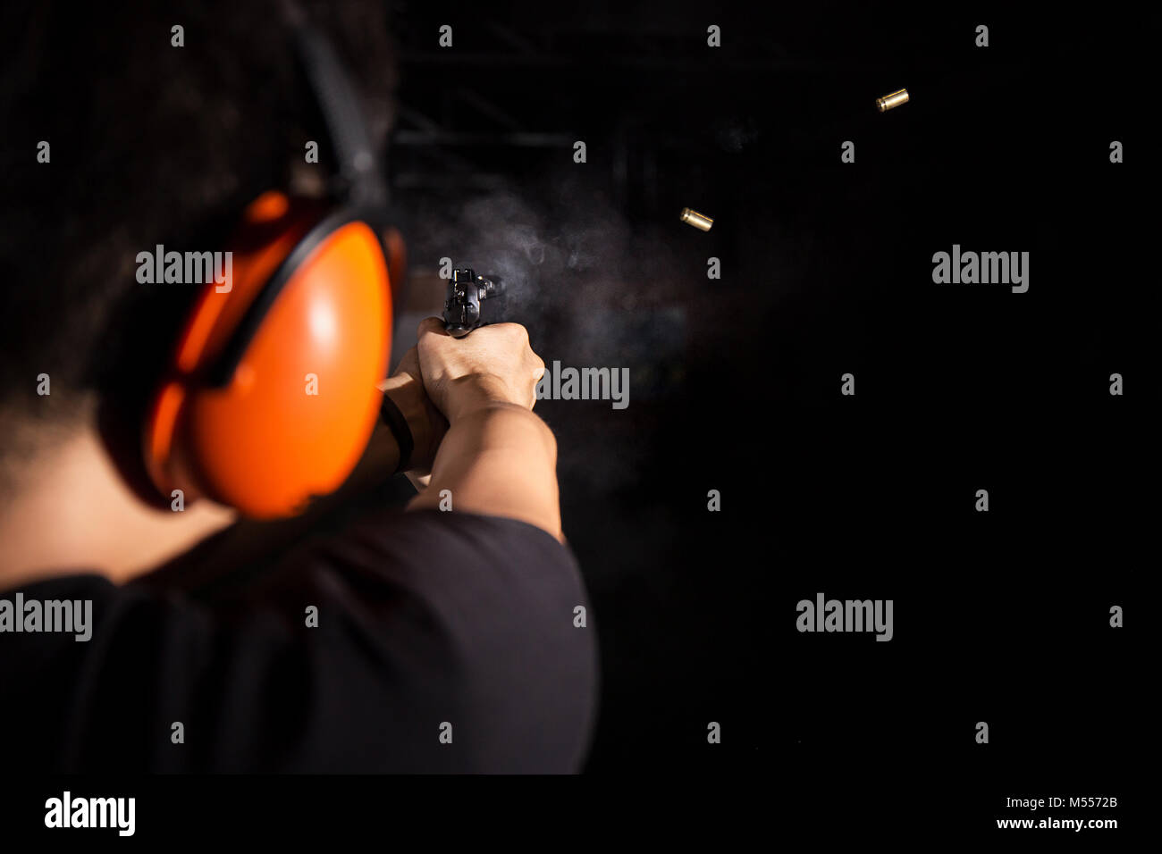 man shooting pistol gun, fire bullet, and wear orange ear cover in shooting range - Stock Image