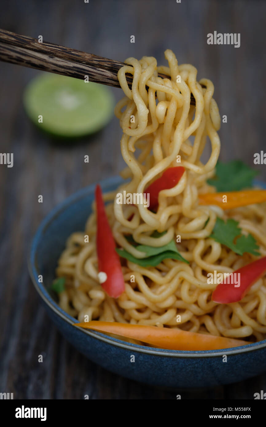 Still life instant noodles with sliced bell pepper on chopstick, junk food or fast food concept. - Stock Image