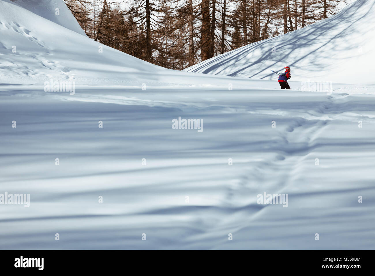 Kid skier skiing down the slope - downhill in high mountains. - Stock Image