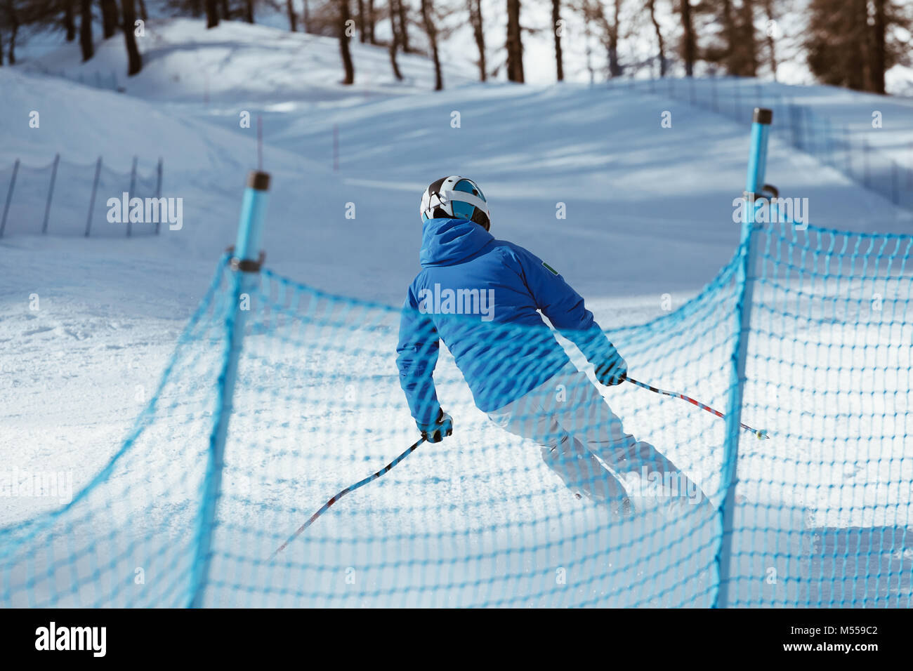 Skier skiing down the slope - downhill in high mountains. - Stock Image