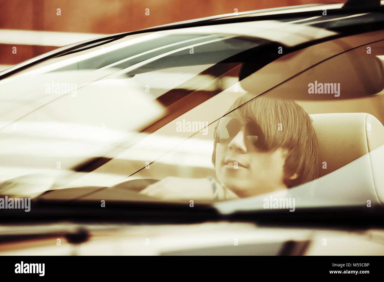 Young man driving convertible car - Stock Image