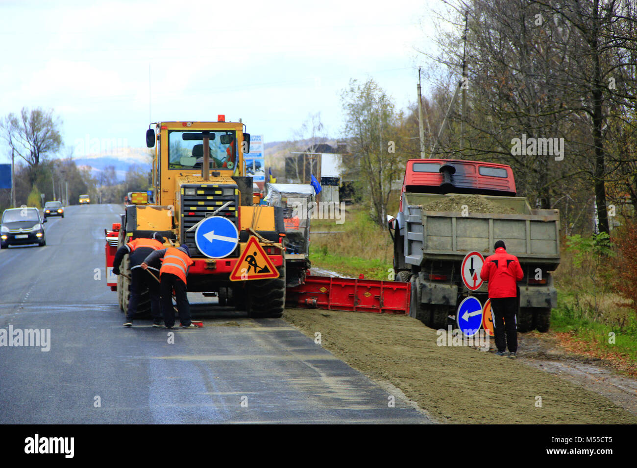 road-roller and repairmen make a repair of the asphalted road Stock Photo