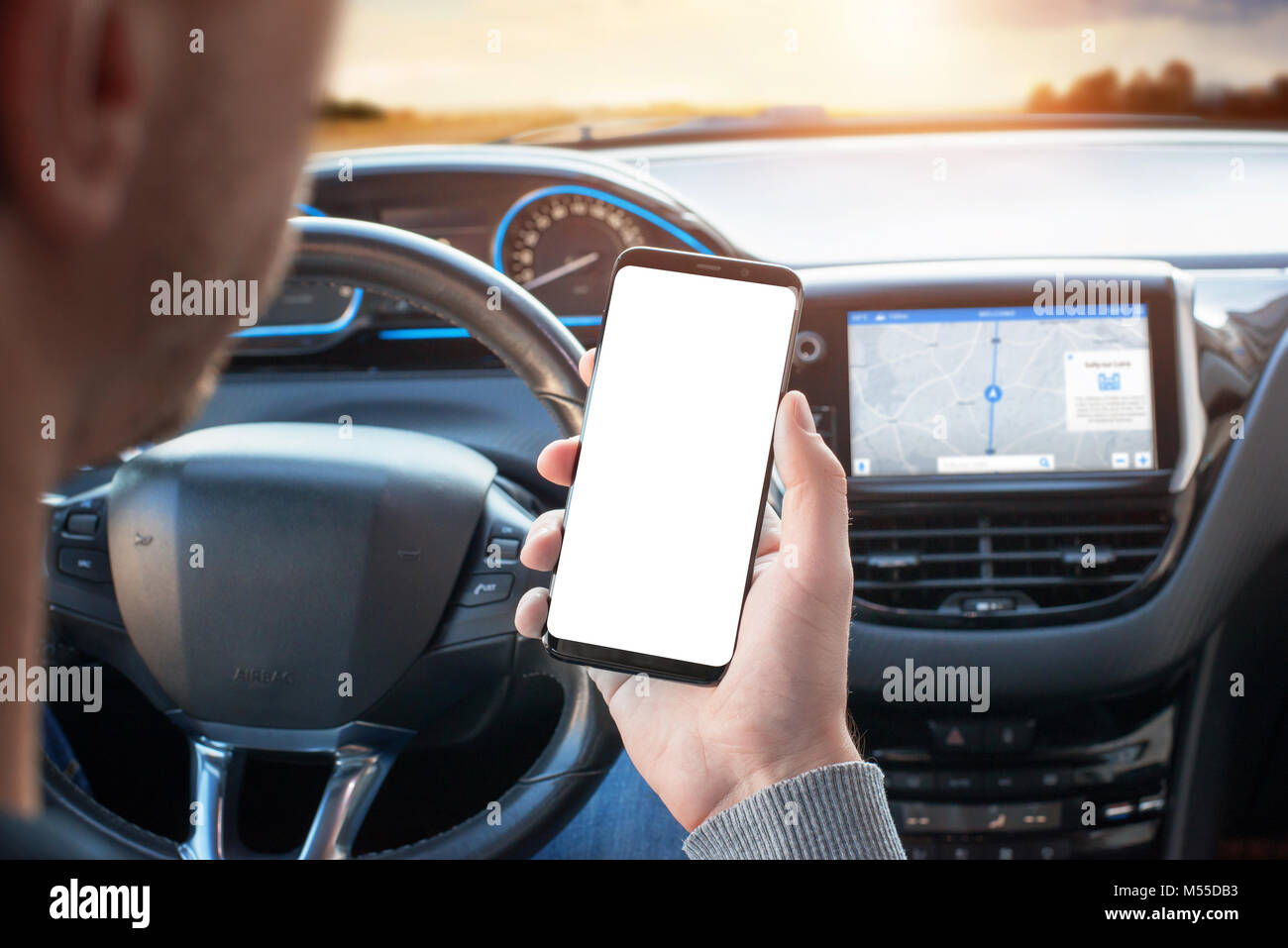 The driver uses the phone while driving. Modern smart phone with round edges. Isolated screen for mockup. Car navigation - Stock Image