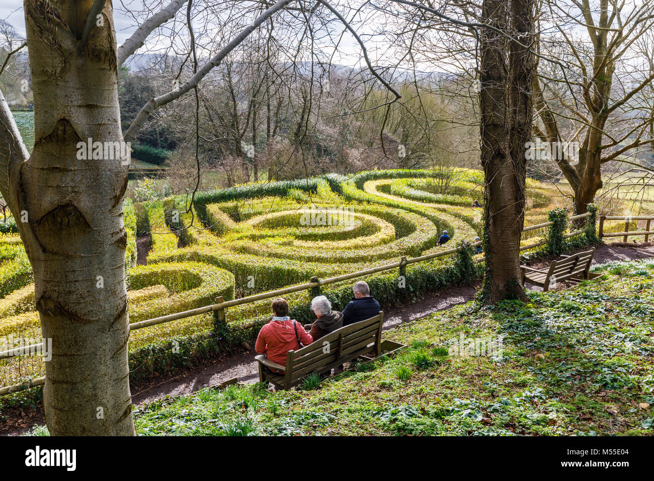 Three people sitting on a bench enjoying a view of The 250 Anniversary Maze at Painswick Rococo Garden, Painswick, - Stock Image
