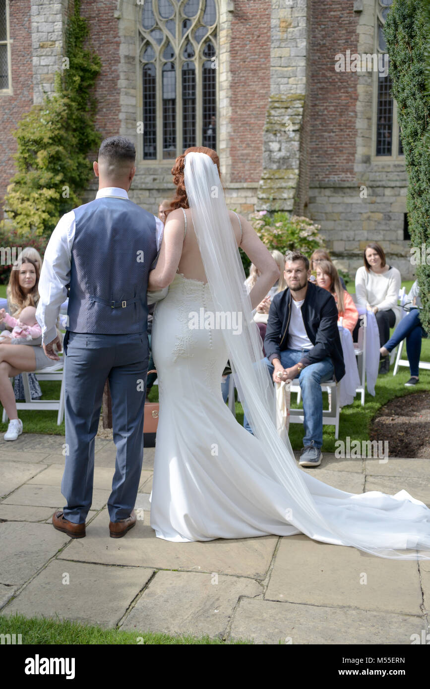 Beautiful Models wearing Bridal wear are walking on a catwalk at Herstmonceux Castle- it is a bright and Sunny day - Stock Image