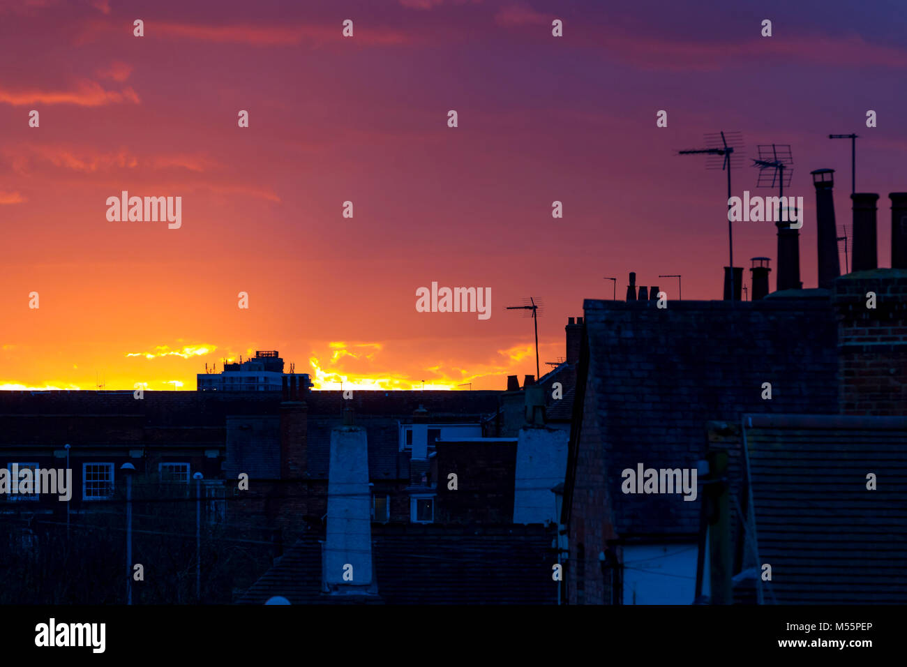 Northampton, U.K. 20th February 2018. Weather. Colourful end to the day looking over the rooftops. Credit: Keith - Stock Image