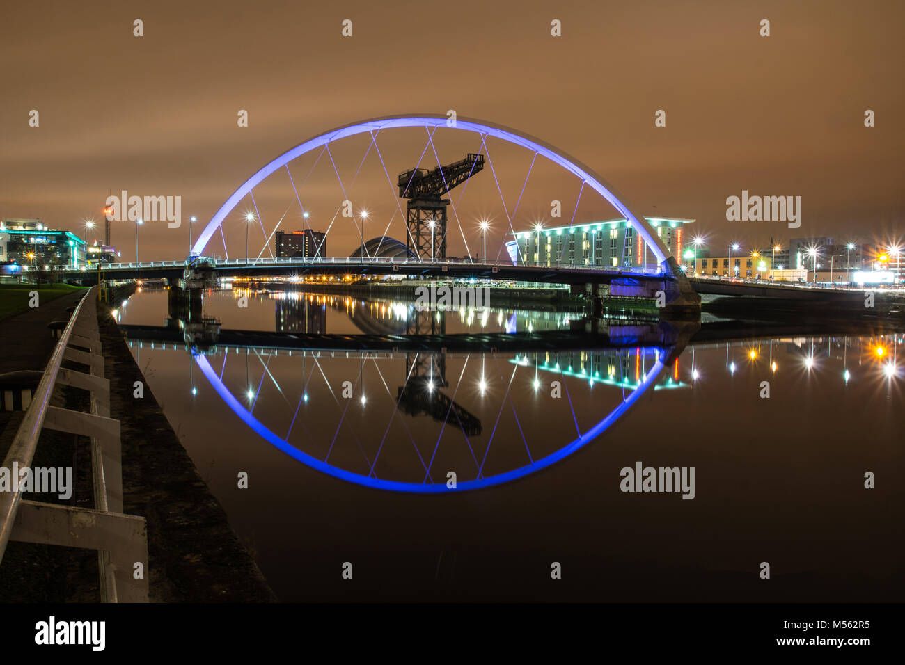 A night shot of the Finnieston Crane also known as the Stobcross Crane, framed in the lights of the Squinty Bridge, - Stock Image