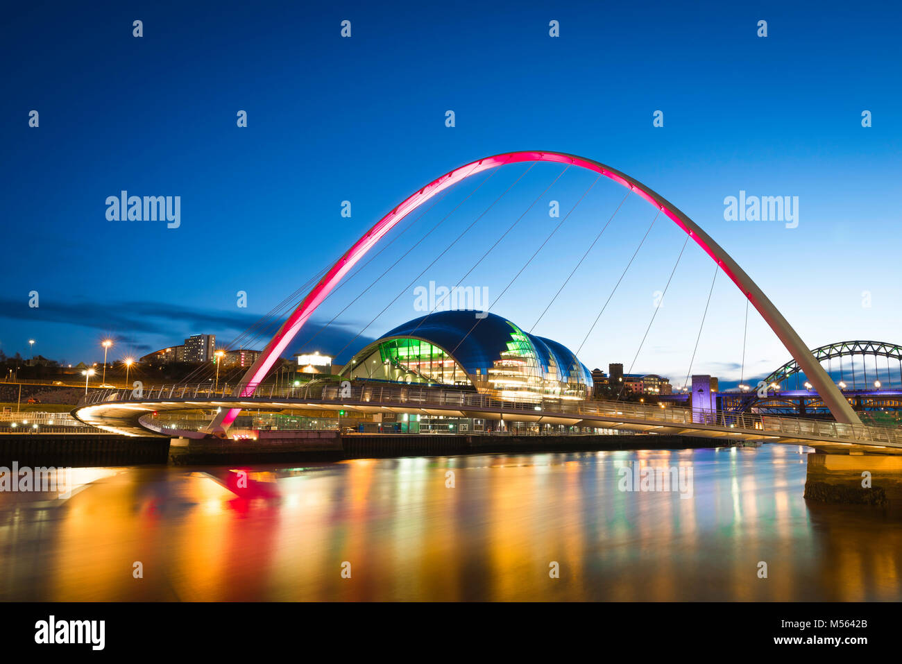 Newcastle upon Tyne UK, view at night of the Sage Gateshead building  and the floodlit Millennium Bridge spanning Stock Photo