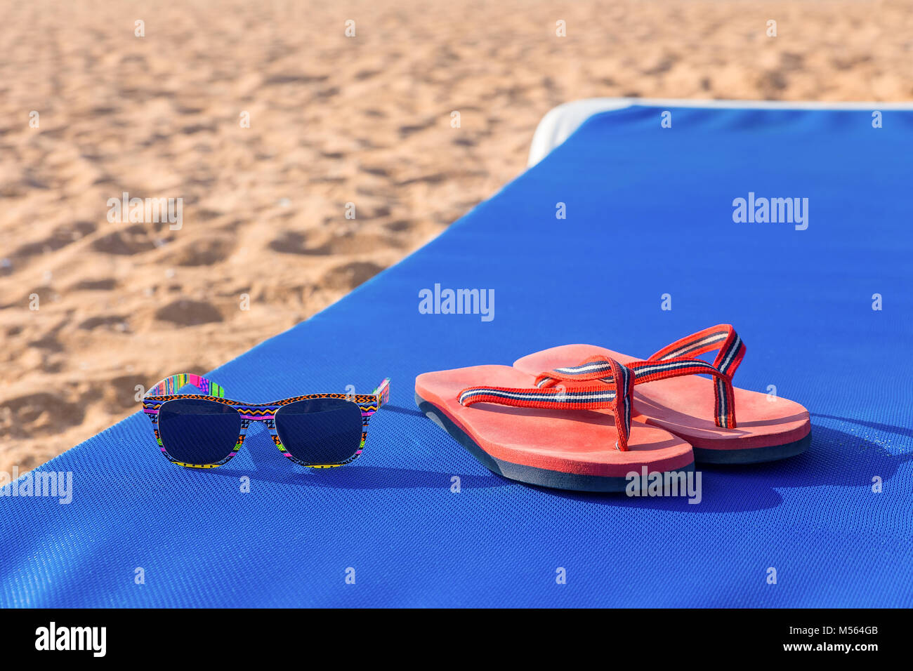 Slippers and sunglasses on sunbed at beach - Stock Image