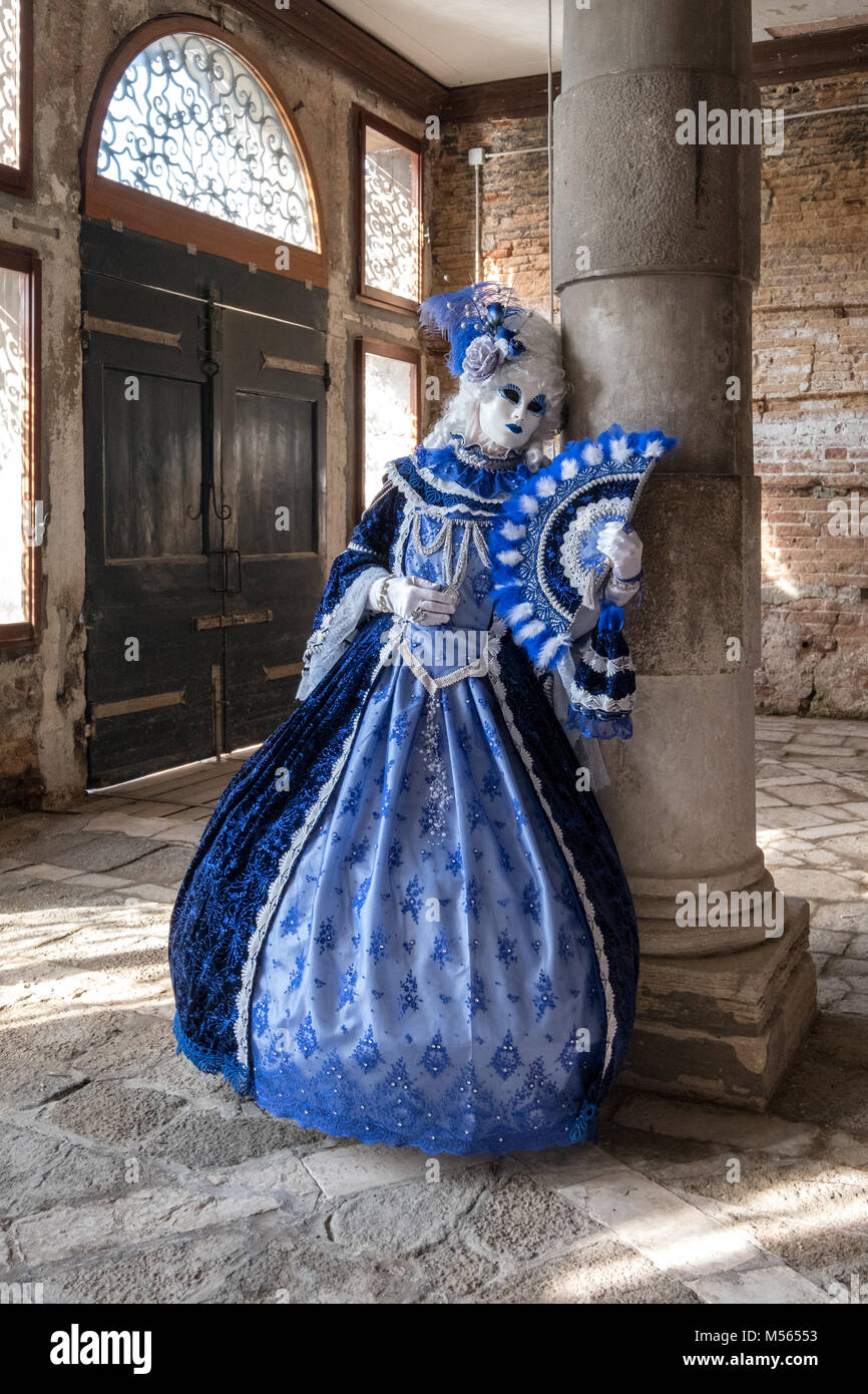Woman in mask and highly decorative blue costume standing next to pillar in old, empty room during Venice Carnival Stock Photo