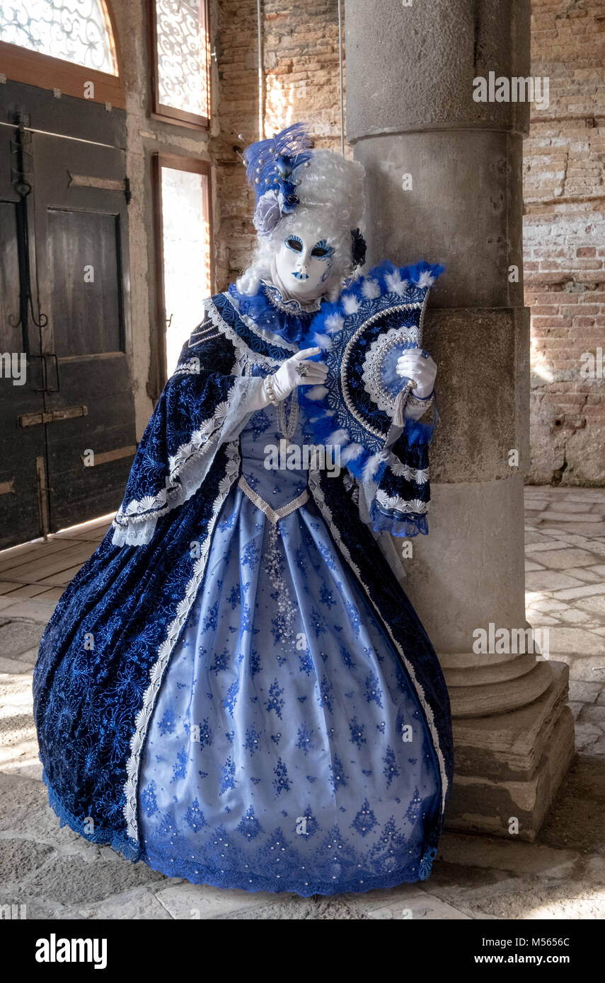 Woman in mask and highly decorative blue costume standing next to pillar in old, empty room during Venice Carnival - Stock Image