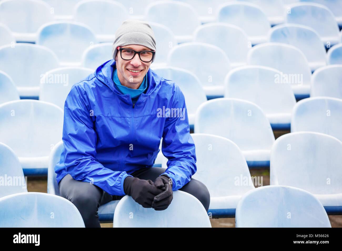 Portrait of professional athlete looking at camera sitting on stadium seat. - Stock Image