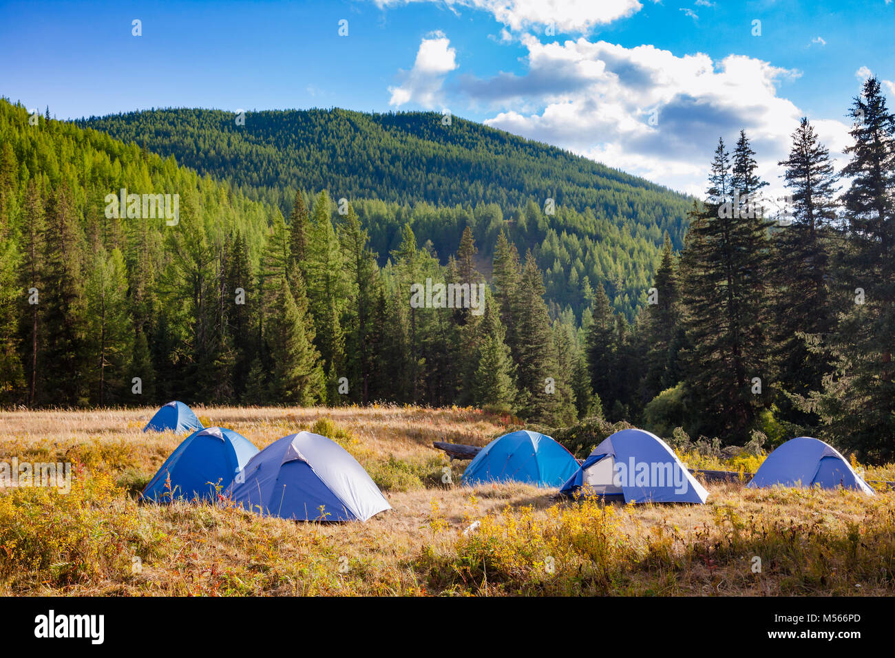 Camping tents on a river shore in wild camping, Altai Mountains, Western Mongolia - Stock Image