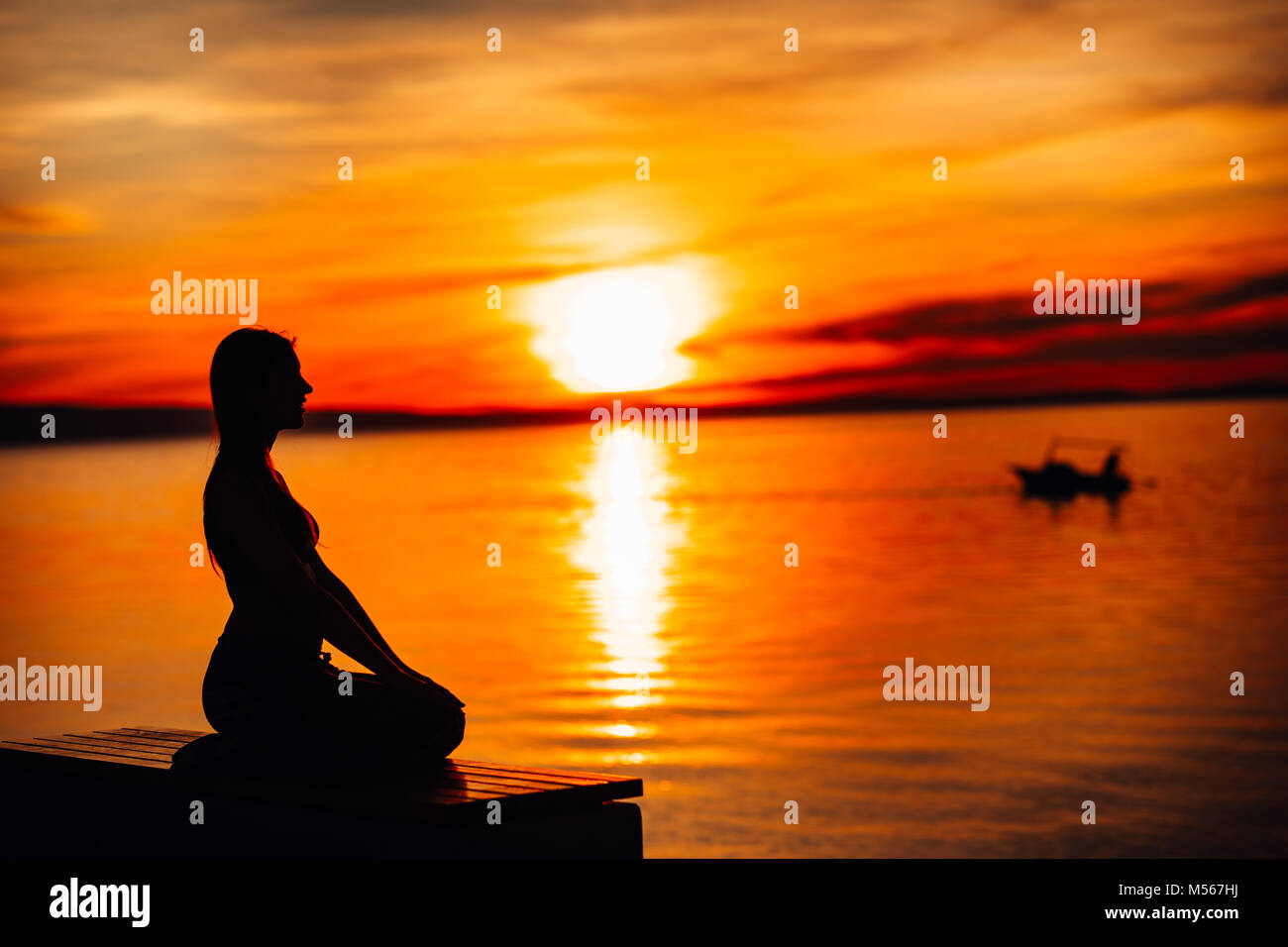 Carefree calm woman meditating in nature.Finding inner peace.Yoga practice.Spiritual healing lifestyle.Enjoying - Stock Image