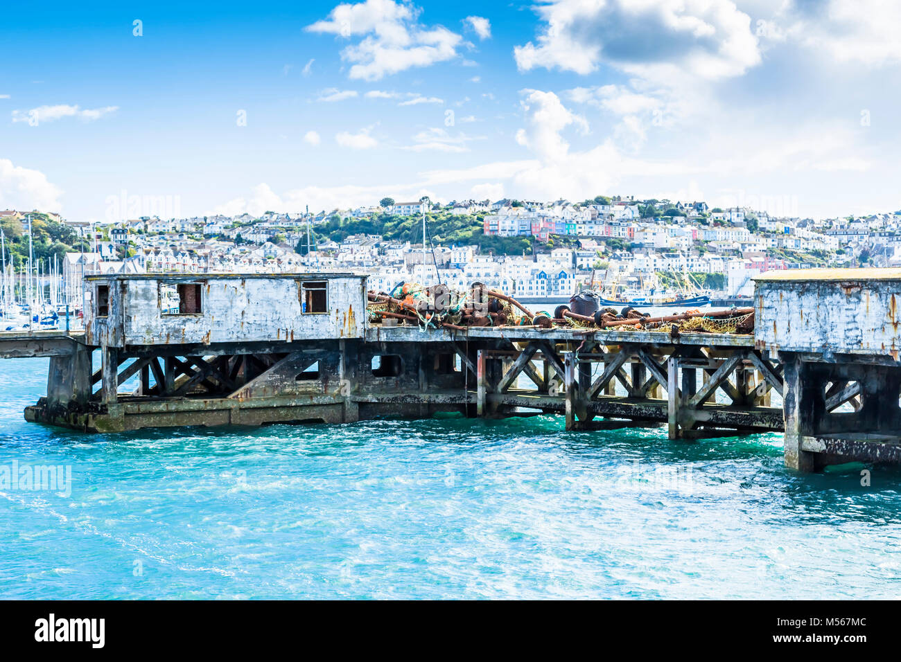 Dilapidated, disused harbour staging in Brixham harbour, South Devon, UK. - Stock Image