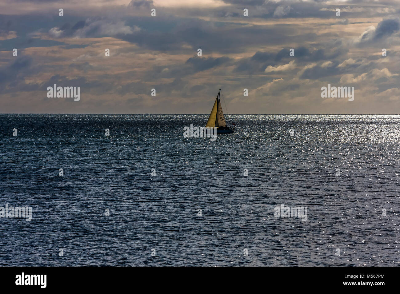 Yacht sailing in Brixham bay in South Devon, UK. - Stock Image
