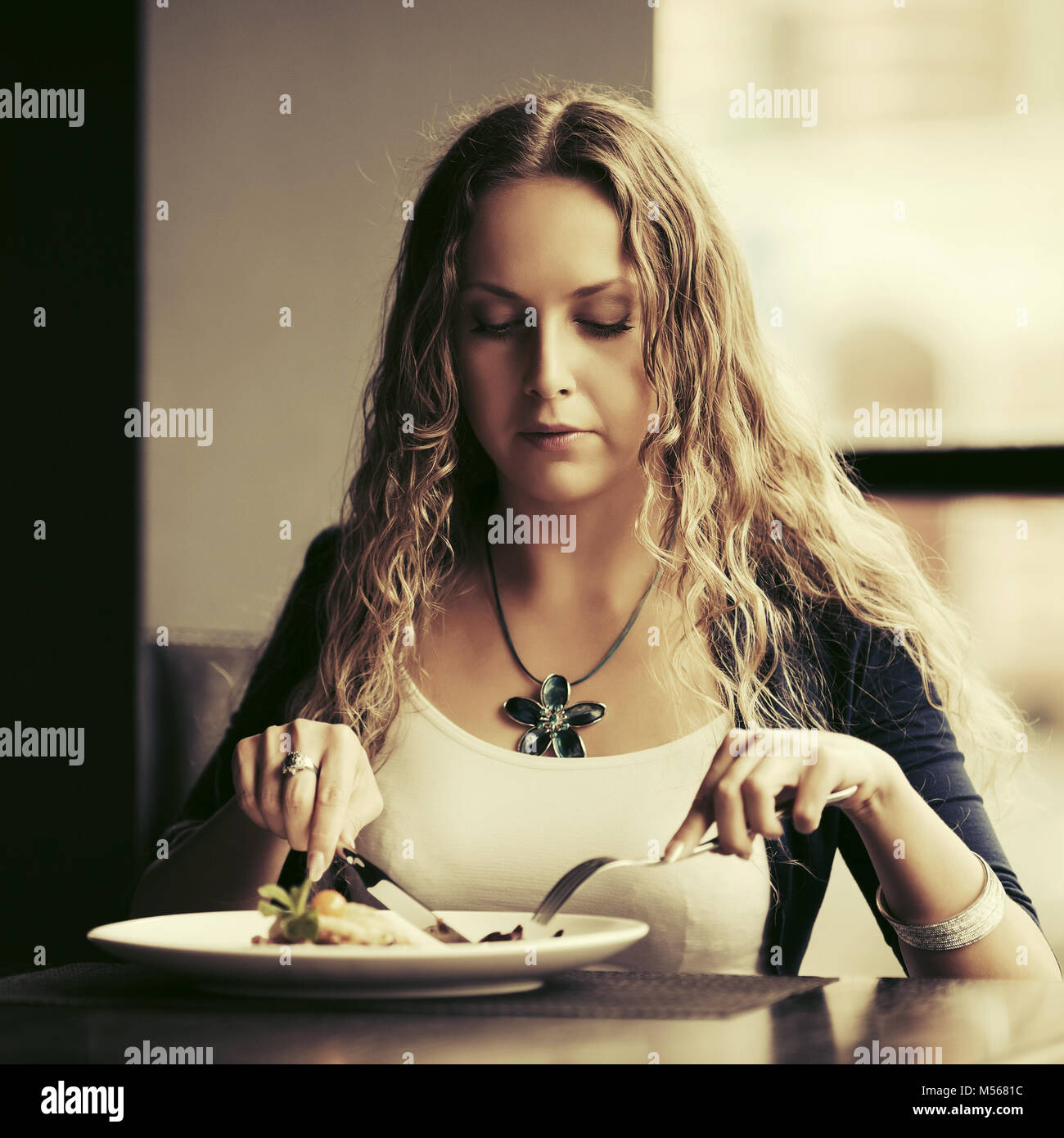 Beautiful young woman dining at restaurant Stock Photo