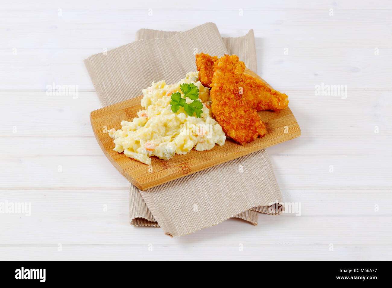 chicken schnitzels with potato salad on wooden cutting board - Stock Image