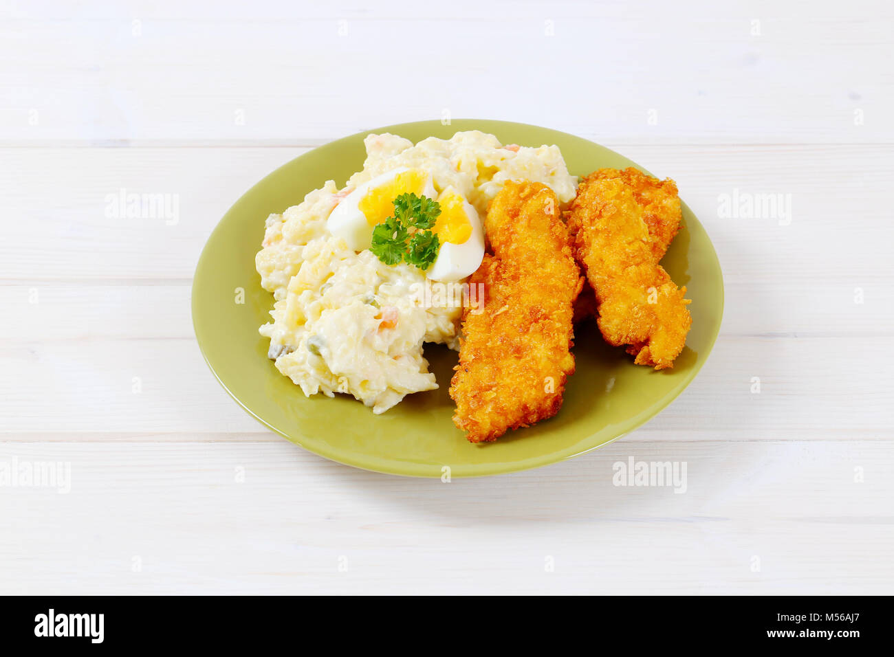 chicken schnitzels with potato salad on green plate Stock Photo