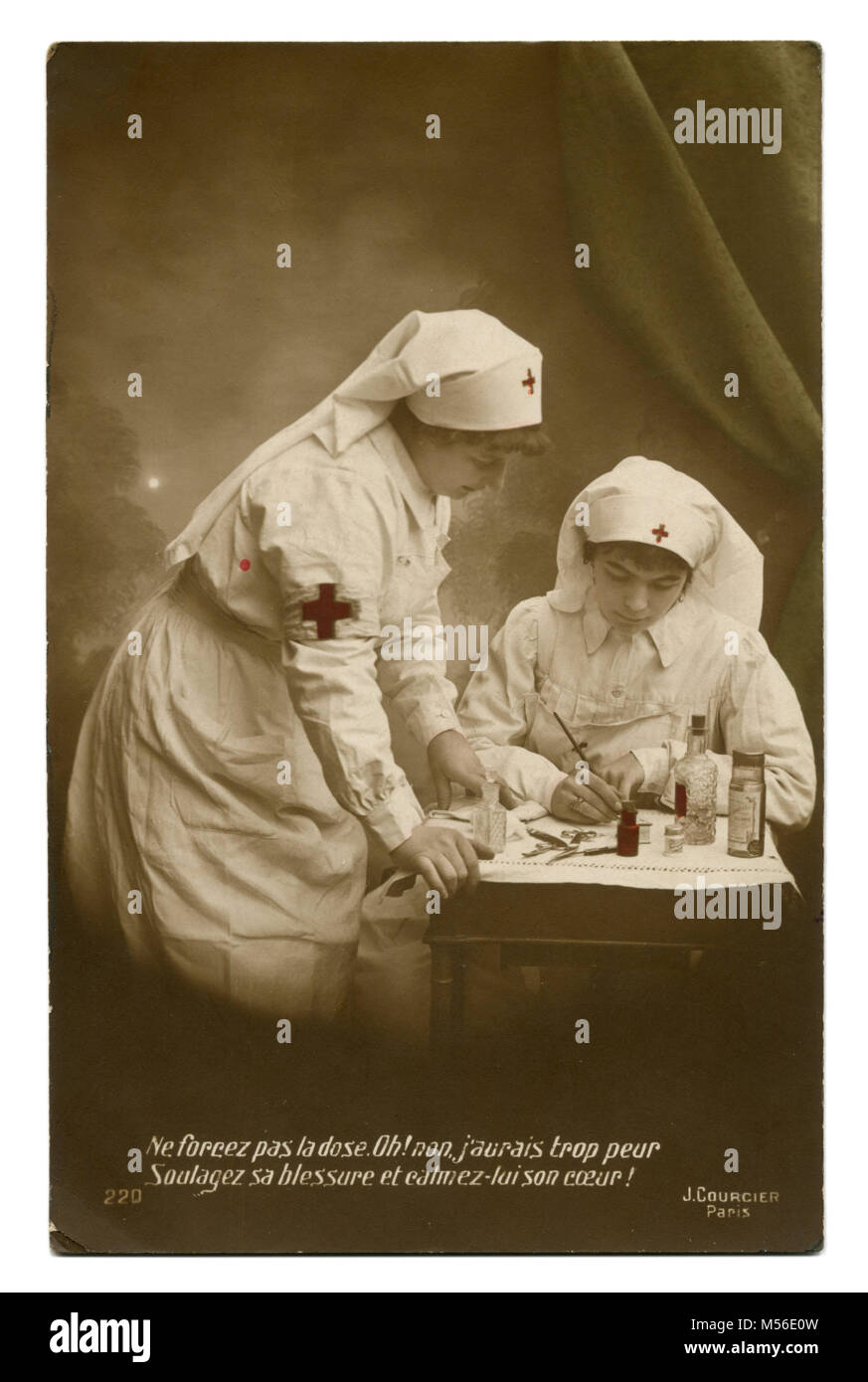 Old French photo postcard: two nurses in white uniform with red crosses with bottles of drugs, writes the diagnosis. - Stock Image